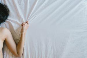 Woman hand grasp bed sheet